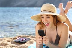 Funny surprised woman watching social media in a smart phone on the beach Stock Image